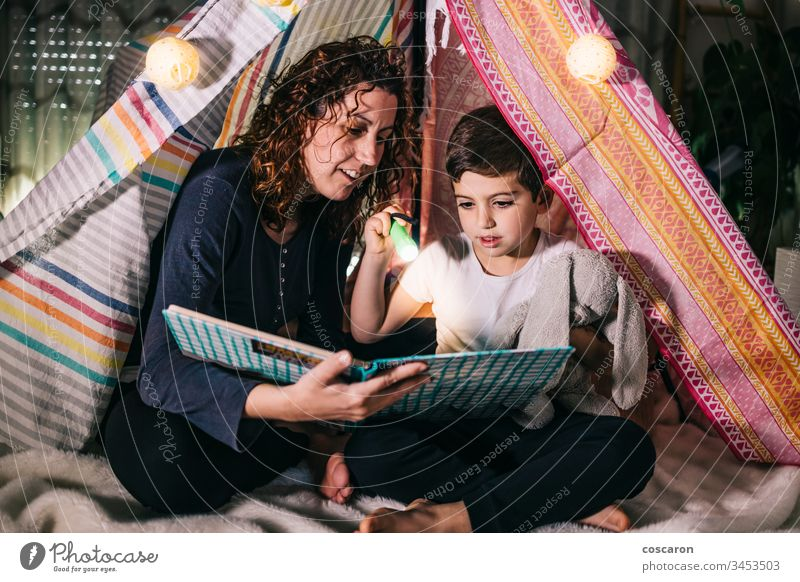 Mutter und Sohn lesen zu Hause auf einem Zelt ein Buch schön Schlafzimmer Schlafenszeit Kaukasier Kind Kindheit Konzept niedlich dunkel Tochter Tag Bildung