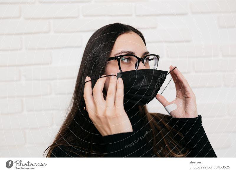 Das brünette Mädchen mit Brille zur Sehkorrektur ist vor einer Virusinfektion geschützt: dem Coronavirus. Eine Frau mit schwarzer medizinischer Maske während der Pandemie 2019-nCoV COVID. der Patient in Quarantäne