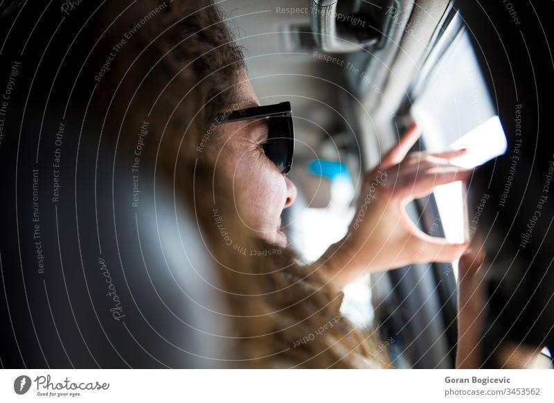Hübsche junge Frau, die auf einer Autoreise ein Foto mit einem Mobiltelefon aus dem Inneren eines Fahrzeugs macht Sitz Blick genießend Ansicht Tag Passagier