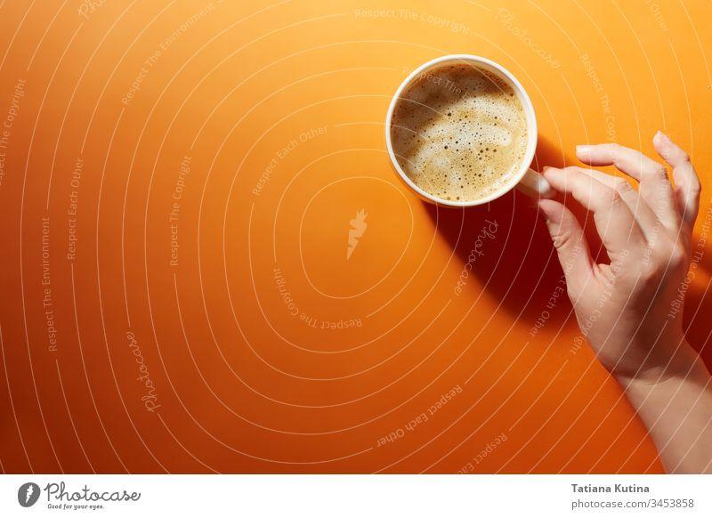 Eine Tasse schwarzer Kaffee mit einer weiblichen Hand auf einem leuchtend orangefarbenen Hintergrund. Minimalismus, Draufsicht. copyspace Becher trinken Design