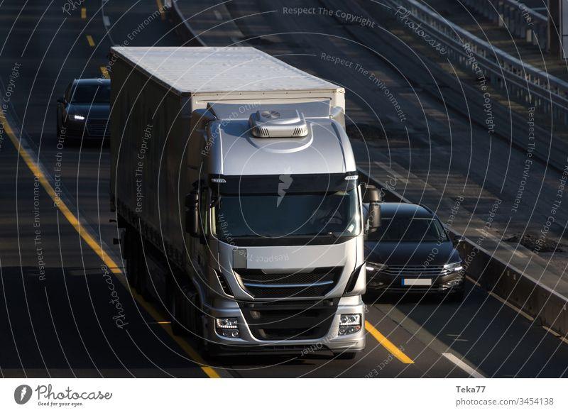 ein moderner grauer Lastwagen, der auf einer Autobahn fährt PKW Ladung Großstadt abschließen Wolken Globalisierung Licht Lichter Ebene Straße Straßen Verkehr