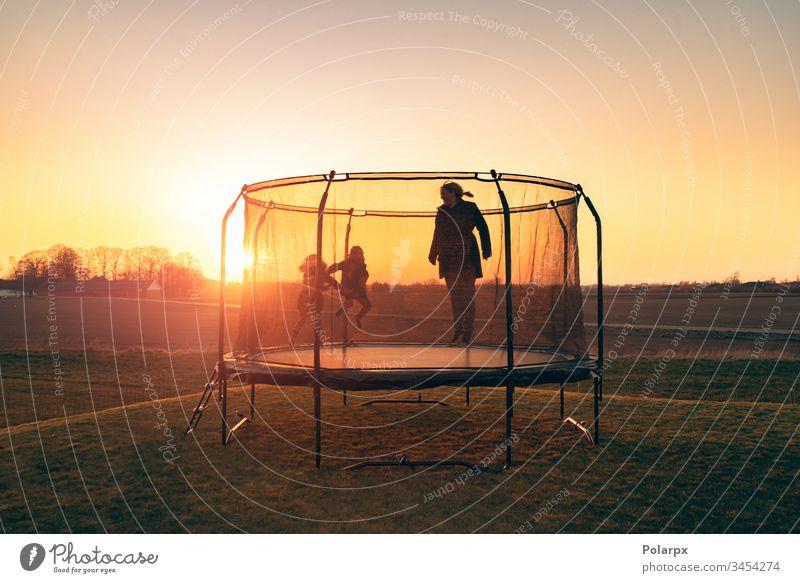 Trampolin auf einer Wiese im Sonnenuntergang mit zwei Kindern Erholung Silhouetten Morgendämmerung Sonnenstrahlen blond Gleichgewicht Aktion Kunstturnen Sport