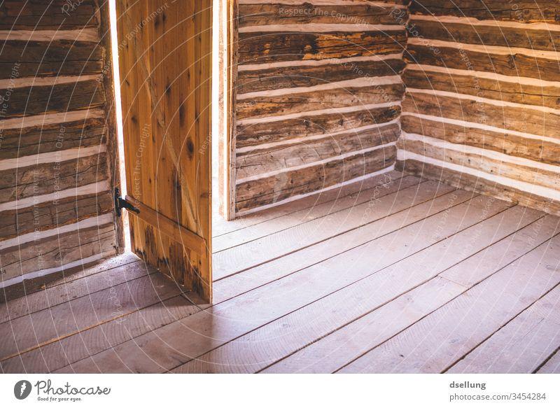 Einfach Holzhütte mit offener Tür Gebäude Abenteuer Gedeckte Farben Verlassenes Haus verlassen Innenaufnahme Einsam ruhig Raum Einfachheit einfach Einsamkeit