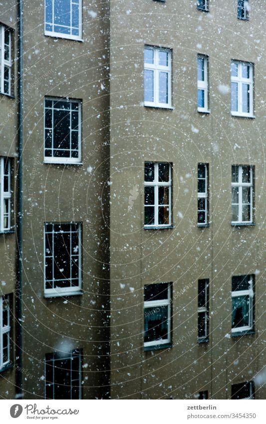 Schneefall vor leeren Fenstern altbau außen fassade fenster haus hinterhaus hinterhof innenhof innenstadt mauer mehrfamilienhaus menschenleer mietshaus schnee