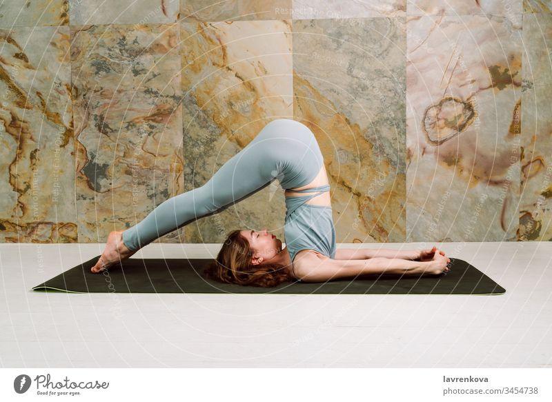 Junge Yogini übt Halasana (Pflug-Pose) in pastellblauen Leggins und oben, selektiver Fokus Pflug-Position aktiv Asana Athlet sportlich attraktiv Körper brünett