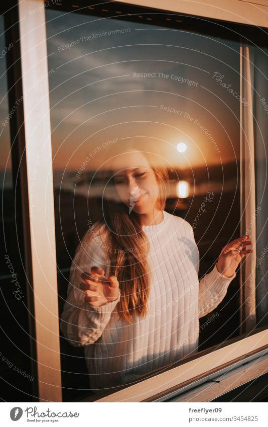 Junge Frau hinter einem Fenster Quarantäne Selbstisolierung Isolation Glas Reflexion & Spiegelung Sonnenuntergang Barriere Coronavirus COVID19 covid-19 orange