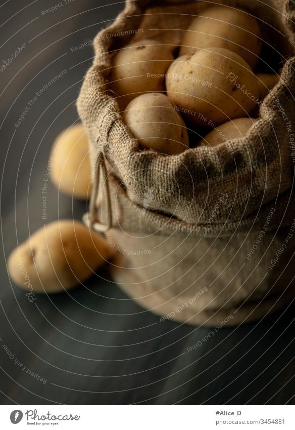 Kartoffeln in Sackleinen auf rustikalem Holzgrund Hintergrund Tasche braun Sack mit Sackleinwand Nahaufnahme kulinarisch Diät Erde erdig fallend Lebensmittel