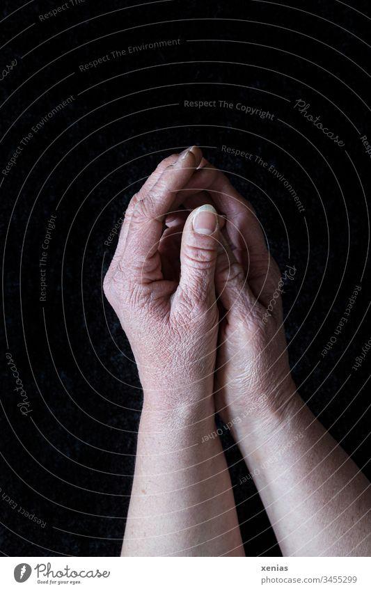 reife Hände, zu oft gewaschen, liegen gefaltet  auf schwarzem Grund, corona thoughts Falten Hand Finger Daumen Fingernagel Mensch Haut Nagel moody