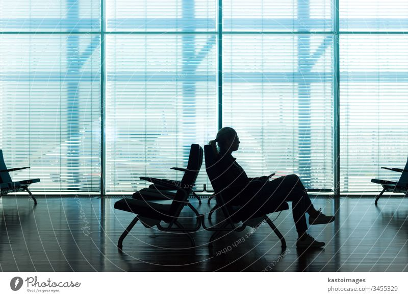 Frau im Transit wartet am Flughafen-Gate. warten Warteraum Wartesaal Wandelhalle Business sitzen Passagier Büro Saal Fenster Glas Jalousien Zeit reisen