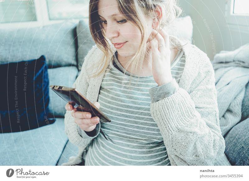 Junge schwangere Frau zu Hause mit ihrem Mobiltelefon Mama Arbeit Telefon heimwärts Quarantäne Schwangerschaft sich[Akk] entspannen Technik & Technologie Job