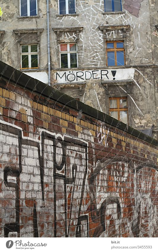 Mörder, steht in schwarzen Buchstaben, als Schriftzug, auf einem alten, besetzten Haus, mit vielen Fenstern, hinter einer mit Graffiti bemalten Backsteinmauer. Hinweisschild als Aufruf gegen Rassismus, Krieg, Hass, Gewalt, Brutalität und Diskriminierung.