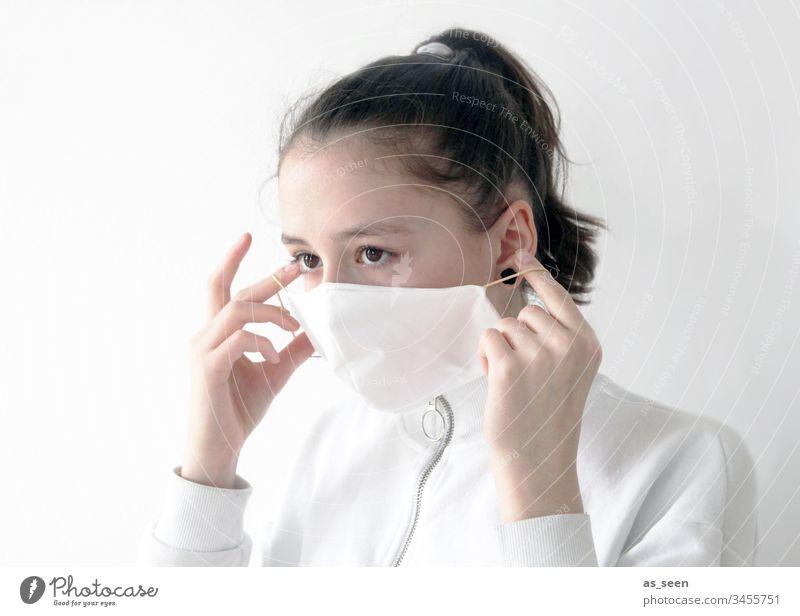 Mädchen setzt Mundschutz auf Atemschutz Atemschutzmaske Maske Mensch Farbfoto 1 Angst Schutz bedrohlich gefährlich Krankheit Coronavirus Infektionsgefahr Virus