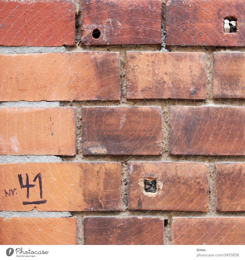 Notlösung ::: handschriftlich notierte Hausnummer auf alter schlecht verfugter Backsteinmauer mit 3 Löchern haus fassade urban Tageslicht Wand kaputt oberfläche