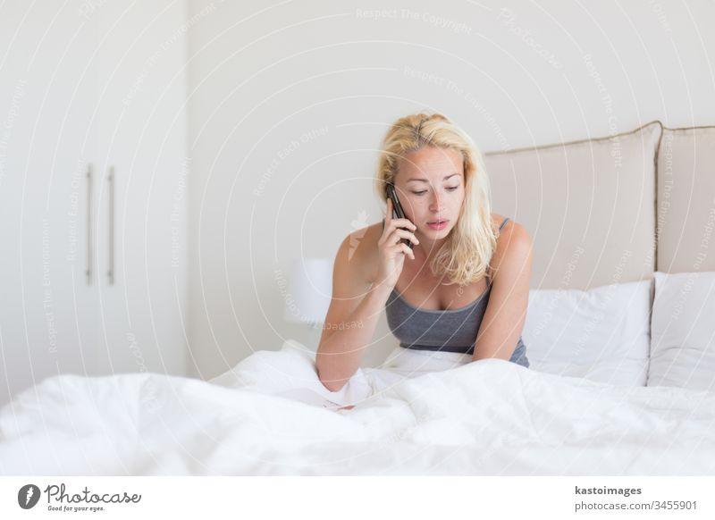 Frau, die morgens im Bett telefoniert. Telefon Anruf Morgen Schlafzimmer reden jung Person Mobile weiß benutzend Kissen Nachrichten heimwärts Raum hören