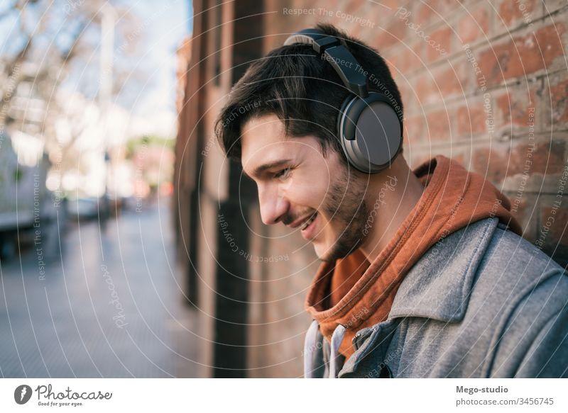 Lateinamerikaner, der mit Kopfhörern Musik hört. Person jung zuhören Menschen Erwachsener Apparatur im Freien Technik & Technologie Lifestyle männlich lässig