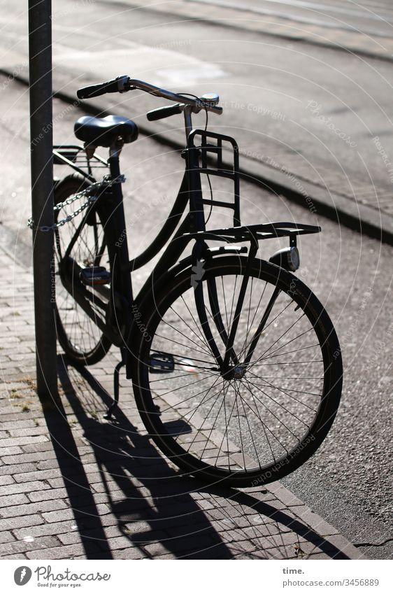 Fiets an Fietspad sonnenlicht morgens linien parallel gegenlicht straße laternenpfahl fahrrad fahrradweg bürgersteig abgestellt pflasterstein gepflastert