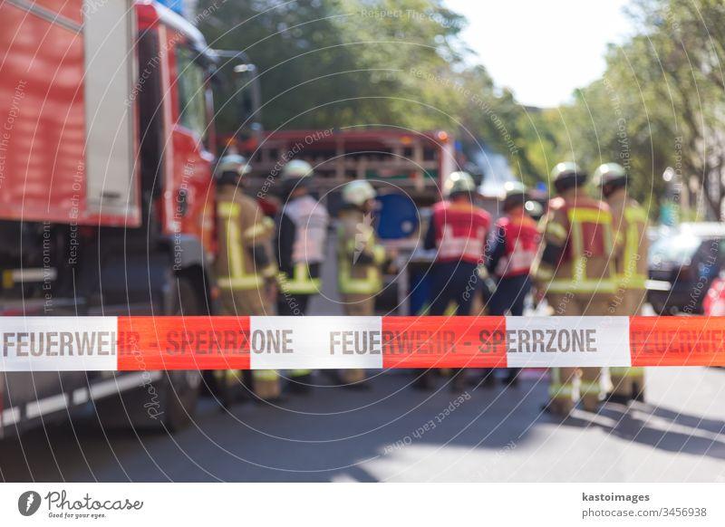 Team von Feuerwehrleuten mit dem Feuerwehrauto am Unfallort. Feuerwehrmann Gerät retten Schutz Brigade Gegend Standort Ermahnung Schutzhelm Notfall Uniform