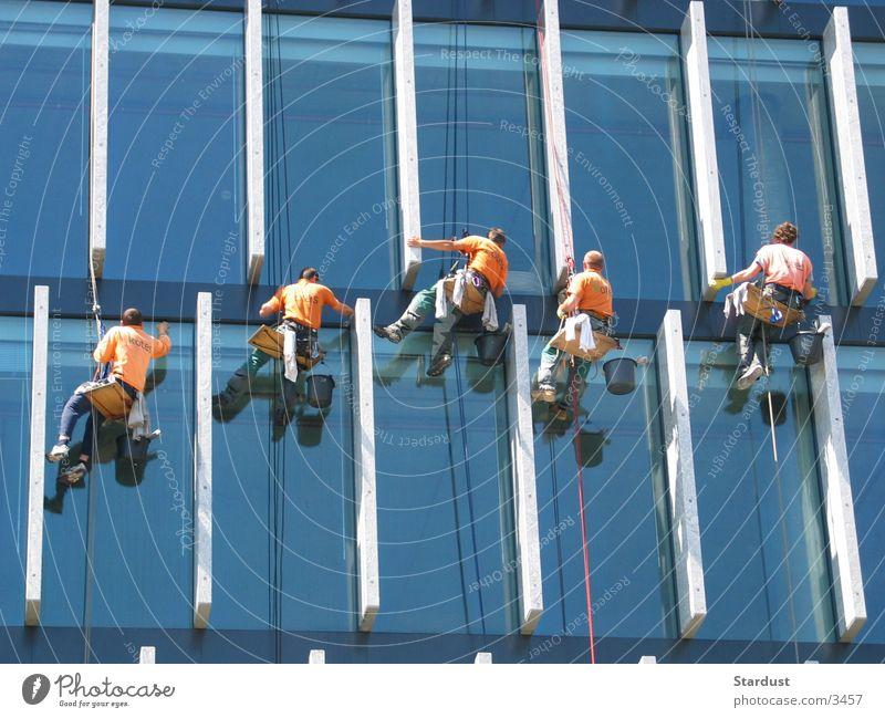 Am seidenen Faden Fenster Menschengruppe Handwerker Hochhaus hoch Reinigen Beruf Gebäudereiniger