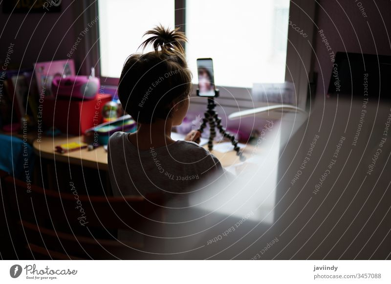 Kleine Mädchen, die sich per Videokonferenz mit einem Smartphone unterhalten heimwärts online Gespräch Einsperrung Freundschaft Internet Kind Talkrunde Tagung
