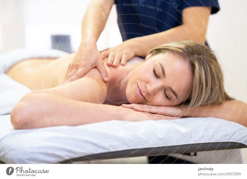 Frau, die auf einer Bahre liegt und eine Rückenmassage erhält. Massage Spa Körper schön Behandlung Lächeln Salon Schönheit Pflege Therapie jung Erholung Mädchen