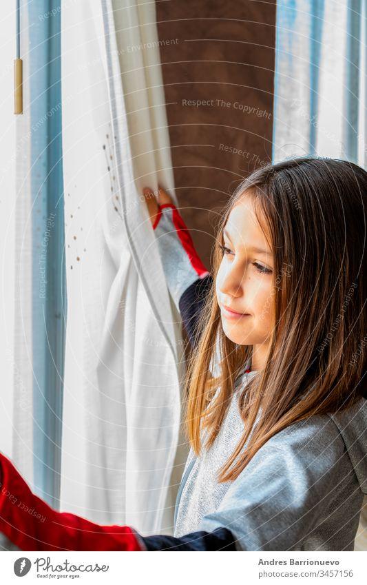 Porträt eines hübschen kleinen Mädchens mit lustiger Haltung, das aus dem Fenster schaut wenig im Innenbereich Kind Frau jung anschauend heimwärts Glas Freunde