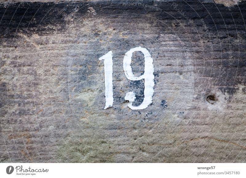 Ziffer 19 auf einer Kalksteinmauer Ziffern & Zahlen Nahaufnahme Außenaufnahme Hausnummer Orientierung Farbfoto