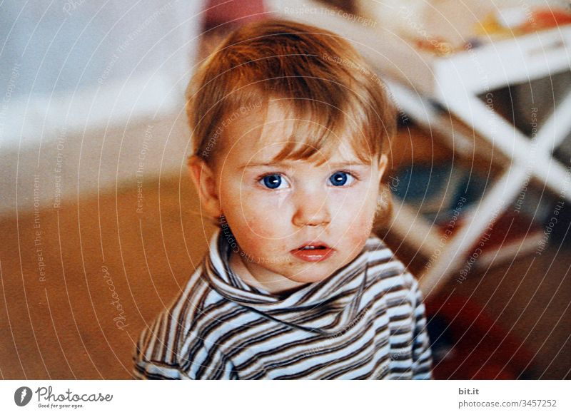 Kleines Mädchen mit leicht verschmiertem Gesicht, zuhause, schaut neugierig in die Kamera. Kind Mensch Kleinkind Porträt Blick Kindheit Blick nach vorn