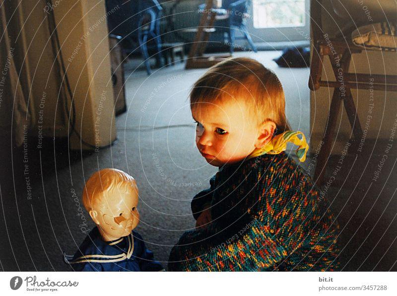 Mitfühlend sitzt das kleine Mädchen zuhause, bei der kaputten Puppe, im Sonnenlicht. Kind Kleinkind Wohnung daheim Spielen niedlich Spielzeug Kindheit Mensch