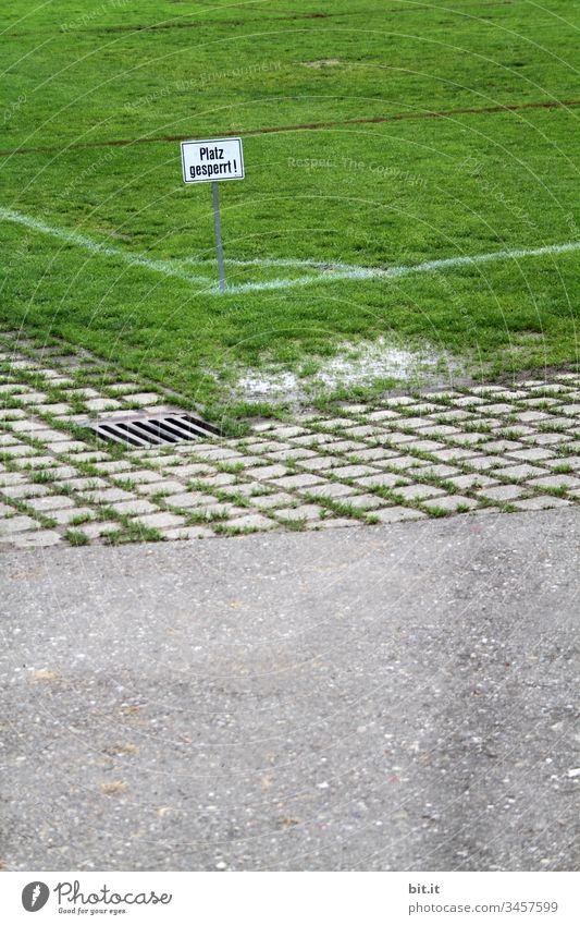 Platz gesperrt, geschrieben auf Schild in der Ecke von einem Sportplatz mit grünem Rasen, neben einer Straße. geschlossen Wort Buchstaben Vorsicht Hinweisschild