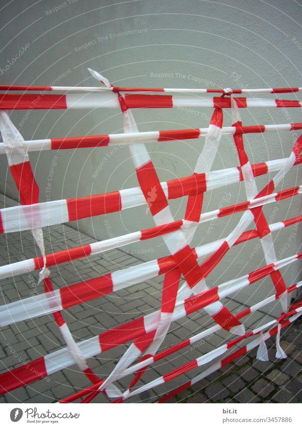 Absperrband, hängt kreuz und quer, über einer Straße, vor einer grauen Hauswand. Sperre Absperrung Durchgang Baustelle Bauarbeiten Menschenleer Barriere
