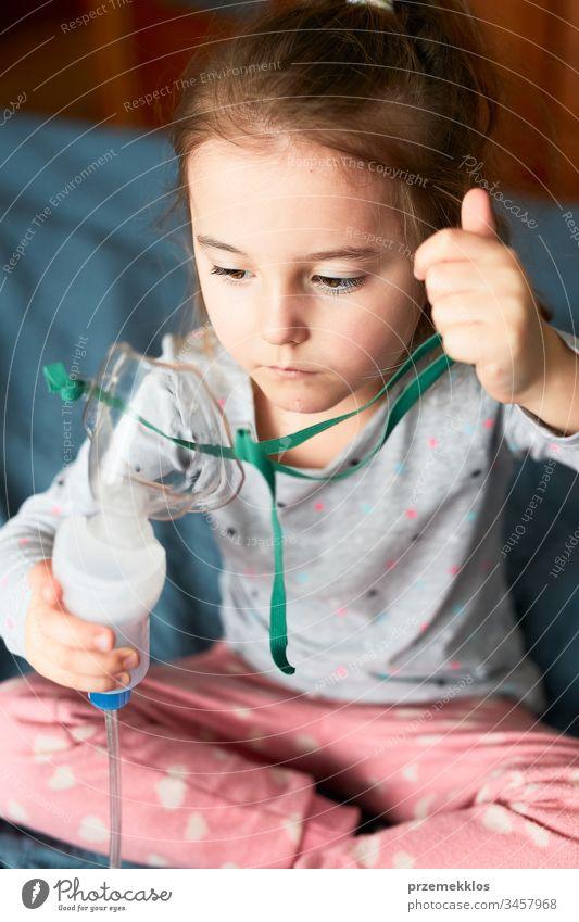 Krankes kleines Mädchen, das eine medizinische Inhalationsbehandlung mit einem Vernebler erhält. Kind mit Atemmaske im Bett sitzend Virus Infektion Arzt Grippe