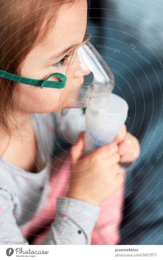 Krankes kleines Mädchen, das eine medizinische Inhalationsbehandlung mit einem Vernebler erhält. Kind mit Atemschutzmaske auf dem Gesicht sitzend im Bett Virus