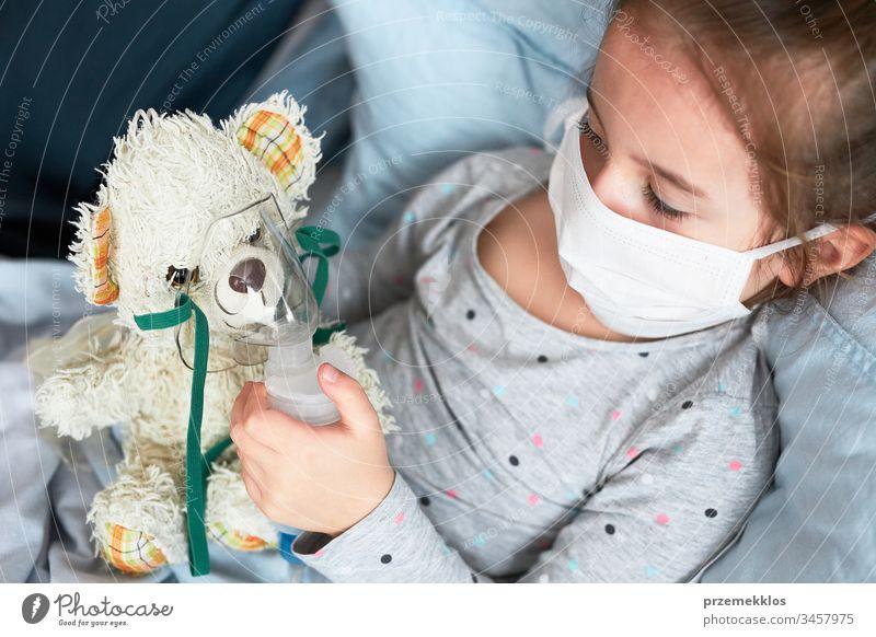 Krankes Kind erholt sich im Bett. Kleines Mädchen spielt, indem es eine medizinische Inhalationsbehandlung mit einem Vernebler an ihrem Teddybär vornimmt. Virus
