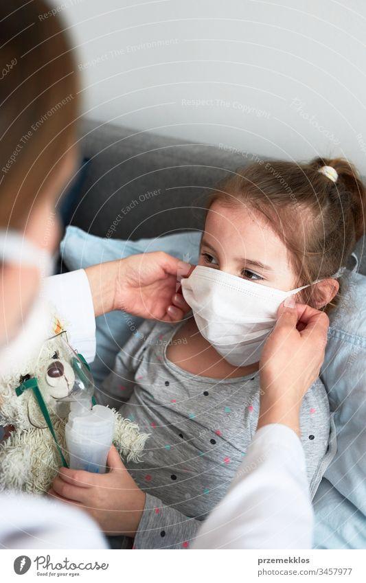Der Arzt bedeckt das Gesicht des kleinen Patienten mit einer Maske. Erkranktes Mädchen bei medizinischer Inhalationsbehandlung mit Vernebler Kind Virus