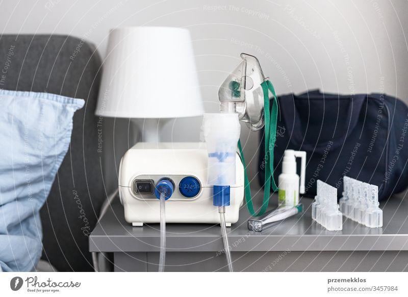 Vernebler mit Atemmaske und Medikamenten auf dem Nachttisch Virus Infektion heimwärts Pflege Bett Krankheit Mundschutz Gesundheit Raum im Innenbereich