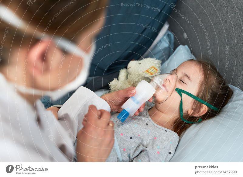 Der Arzt besucht den kleinen Patienten zu Hause. Kind, das eine medizinische Inhalationsbehandlung mit einem Vernebler erhält. Mädchen mit Atemmaske im Gesicht. Frau mit Uniform und Gesichtsmaske.