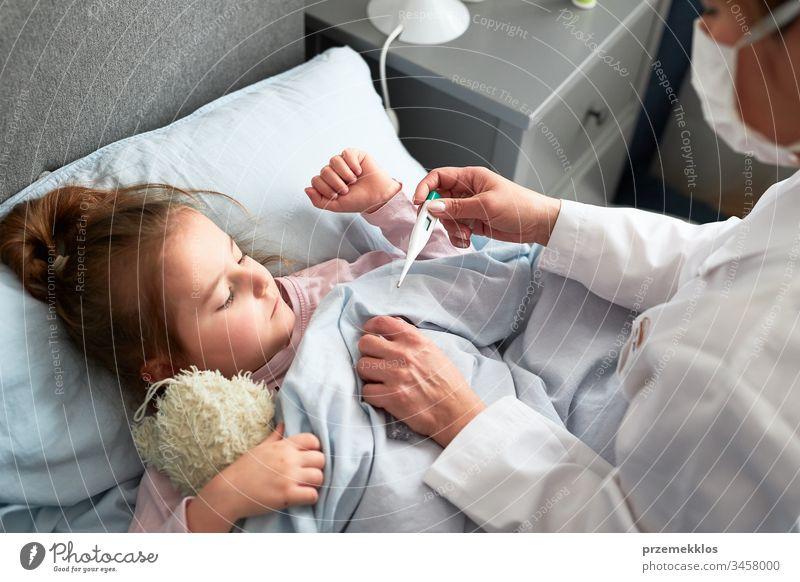 Der Arzt besucht den kleinen Patienten zu Hause. Messung der Temperatur eines kranken Mädchens, das im Bett liegt. Frau trägt Uniform und Gesichtsmaske. Medizinische Behandlung