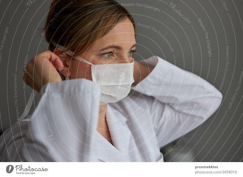Der Arzt bedeckt ihr Gesicht mit einer Maske. Porträt einer jungen Frau, die die Uniform und die Maske trägt, um eine Virusinfektion zu vermeiden und die Ausbreitung der Krankheit zu verhindern. Echte Menschen, authentische Situationen