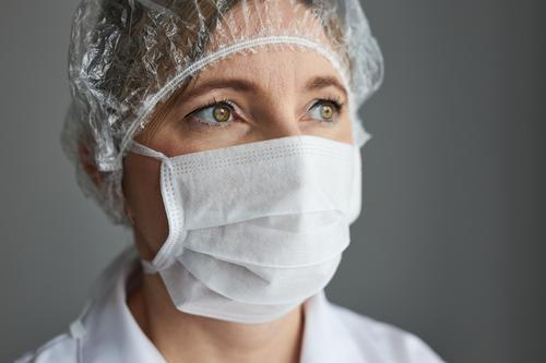 Arzt mit maskiertem Gesicht. Porträt einer jungen Frau, die Uniform, Mütze und Maske trägt, um eine Virusinfektion zu vermeiden und die Verbreitung von Krankheiten zu verhindern. Echte Menschen, authentische Situationen