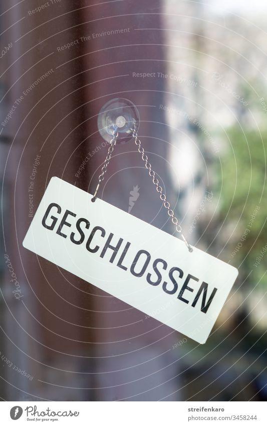 """Schild """"Geschlossen"""" hängt an einer Glasscheibe, in der sich die Umgebung spiegelt Laden Geschäft geschlossen Gebäude Corona Corona-Virus Krise Coronakrise"""