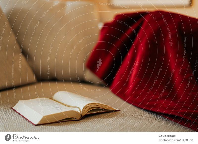 Buch liegt auf gemütlicher Couch mit roter Decke stayhome lesen aufgeschlagen beige Erholung stay at home ruhen Geborgenheit Rückzug kontemplativ Lifestyle