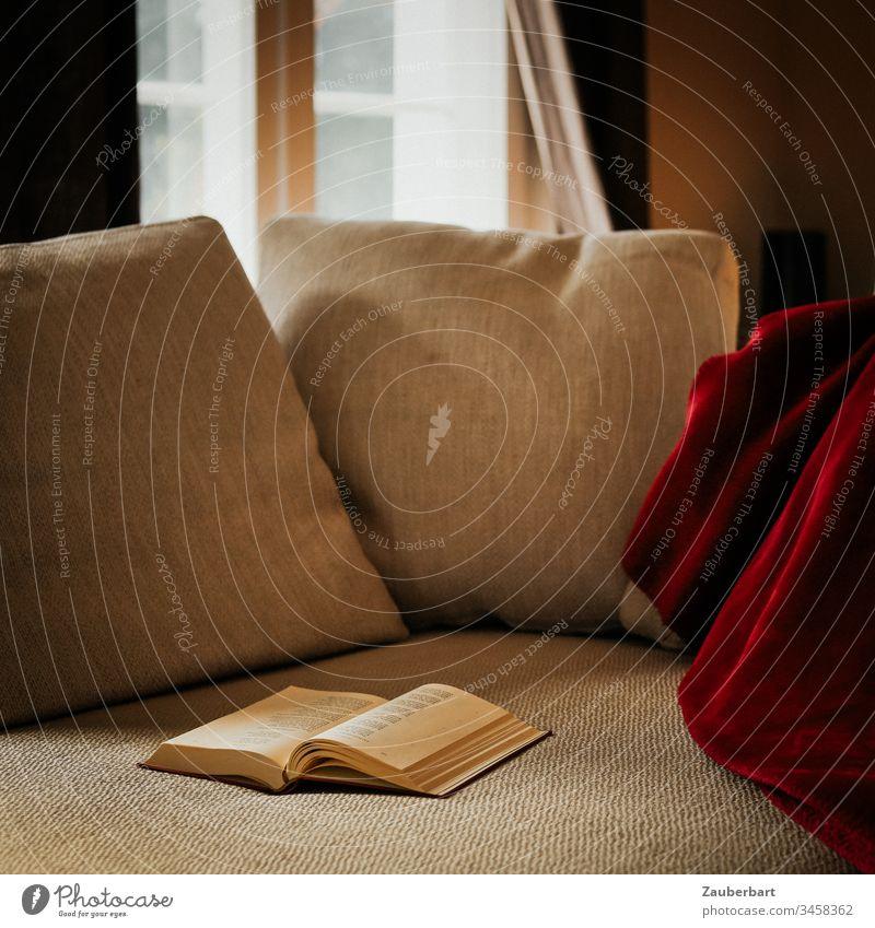 Gemütliches Sofa mit Kissen, roter Decke und Buch, im Hintergrund Sprossenfenster, als Leseplatz zuhause stayhome lesen gemütlich Fenster Tageslicht beige