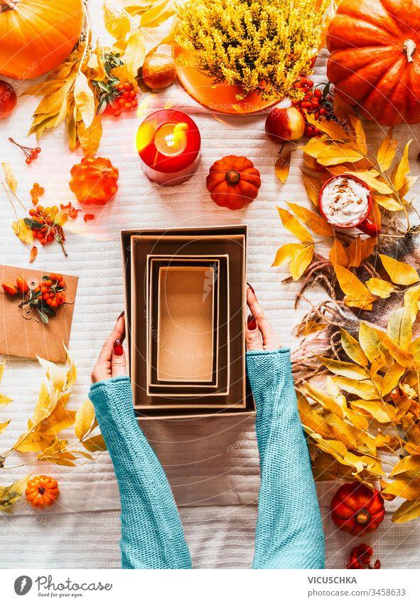 Frauenhände in blauem Pullover halten leere umweltfreundliche Bastelkartons mit verschiedenen Kürbissen, Herbstblättern, Kerzen und Cappuccino in rotem Becher auf weißem Deckenhintergrund auf dem Schreibtisch. Ansicht von oben. Flach gelegt