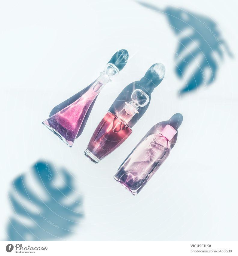 Rosa Kosmetikproduktflaschen im Sonnenlicht auf weißem Hintergrund mit tropischen Monsterblättern im Schatten. Ansicht von oben. Moderne Hautpflege. Parfüms. Flach liegend. Durchsichtig. Schönheitskonzept