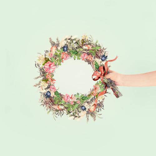 Weibliche Frauen halten in der Hand einen Sommerblumenkranz mit Band auf hellem Minze-Hintergrund. Kreatives Blumenarrangement-Konzept Beteiligung Totenkranz