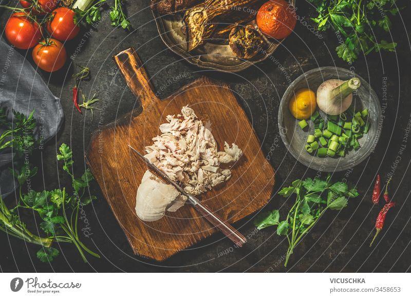 Gezogene Hühnerbrust auf Schneidebrett mit Messer mit Gemüsezutaten auf dunklem, rustikalem Hintergrund. Ansicht von oben. Gesunde Ernährung. Kohlenhydratarme Fitness-Diät. Leichtes Kochen