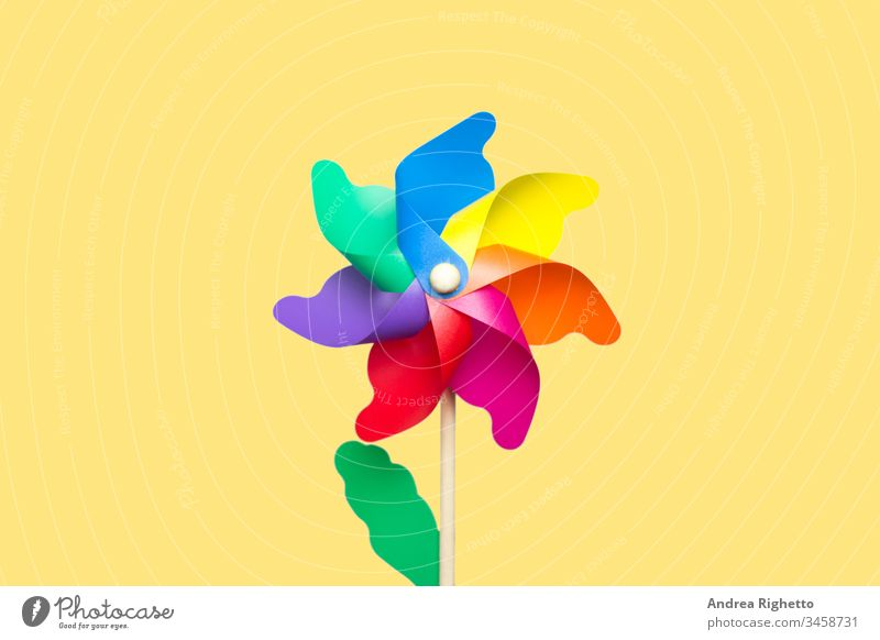 Konzept von LGBT, lesbische und schwule Menschen, nostalgische Kindheit, Regenbogenfahne. Regenbogen-Pinwheel in der Mitte des Bildes mit gelbem Hintergrund. Isoliertes