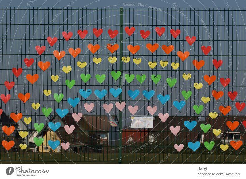 Regenbogen gegen Corona an einem Zaun, bestehend aus vielen kleinen bunten Herzen, als Zeichen der Solidarität mehrfarbig Farbfoto Außenaufnahme Einsamkeit