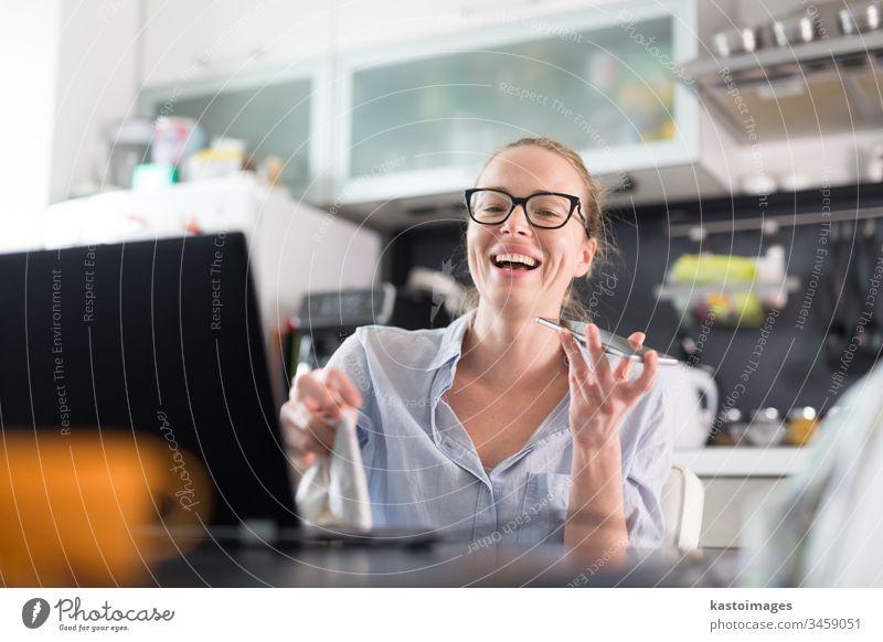 Bleiben Sie zu Hause und distanzieren Sie sich von der Gesellschaft. Frau in ihrer lässigen Hauskleidung, die fern vom Küchentisch arbeitet. Videochatten über soziale Medien mit Freunden, Familie, Geschäftskunden oder Partnern