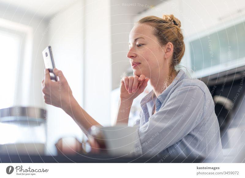 Junge, lächelnde, fröhliche, zufriedene Frau, die zu Hause in der Küche sitzt und soziale Medien auf dem Handy nutzt, um mit ihren Lieben zu plaudern und zu stylen. Bleiben Sie zu Hause, sozialer distanzierender Lebensstil.